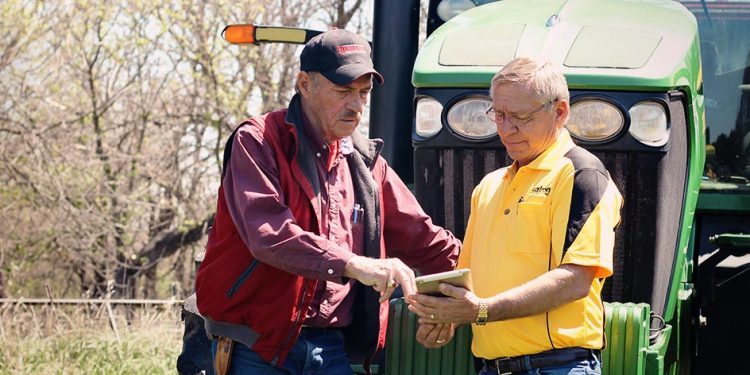 Farmer and Sales Rep looking at an iPad next to a John Deere Tractor