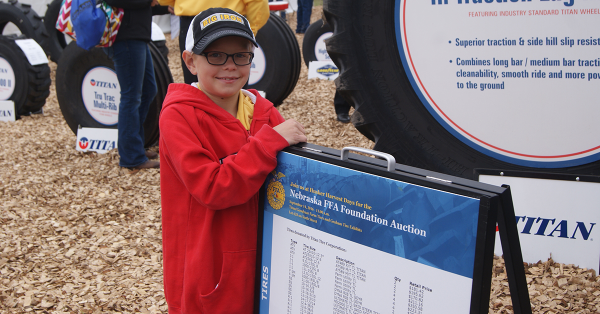 Boy standing with FFA Tire Auction Sign
